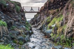 Stream flowing into the sea. Through the colorful gorge, under the old bridge on a cloudy autumn afternoon Royalty Free Stock Images
