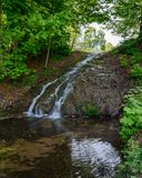 A stream flowing though Himley Hall Park in Dudley, West Midlands, UK in the autumn. Previously the home of the Earl of Dudley. A cascade of water flowing though stock photo