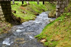 Stream with flowing water under the bridge Royalty Free Stock Photo