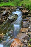 The stream flowing water. Use a low shutter speed to shoot the stream water like clouds or satin.There are green grass and stones by the river stock photos