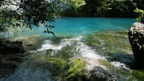 The stream flows into the blue mountain lake.  stock video footage
