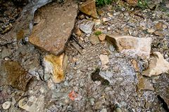 Stream flows through limestone rocks and pebbles. A shallow stream flows through limestone rocks and pebbles Royalty Free Stock Photography