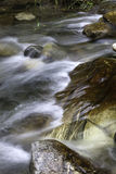 Stream flows over large rock. Royalty Free Stock Image