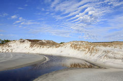 Stream Flows Through the Sand Dunes to Ocean Stock Image