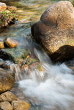 Stream flows through small rocks Stock Photo