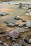 Stream flows through small rocks Stock Photos