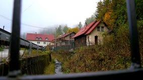 Stream flows through the village. Narrow stream flows through in the slovak village stock video footage