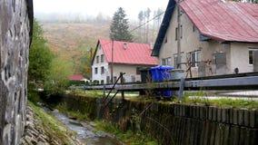 Stream flows through the village. Narrow stream flows through in the slovak village stock footage