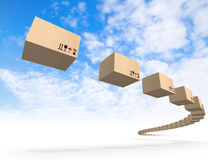 Stream of flying cardboard boxes above blue sky Royalty Free Stock Photos