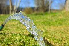 A stream of fresh, clean, cool water from a watering hose. Concept: watering plants in the garden, clean water at a country site. Health and Ecology royalty free stock photography