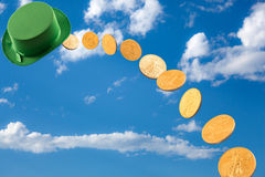 Stream of gold coins falling from blue sky Royalty Free Stock Image