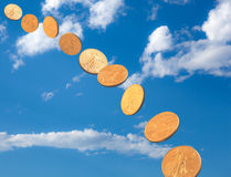 Stream of gold coins falling from blue sky Royalty Free Stock Photography