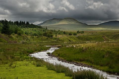 Stream in landscape leads to mountains in distance. Beautiful landscape across countryside to mountains in distance with moody sky Royalty Free Stock Photo