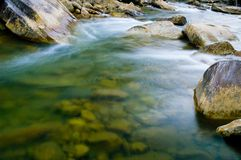 Stream in motion. Time exposure of stream rushing by Royalty Free Stock Photography
