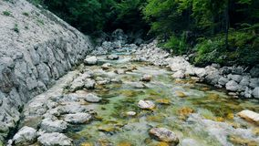 A stream mountain river is flowing down the rocks surrounded by green trees. A stream is flowing down the rocks surrounded by green trees. 4K stock video footage