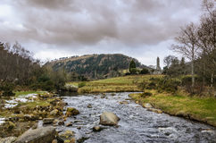 Stream Near The Round Tower. This is a stream near the monastic ruins in Glendalough, Ireland. In the distance is the round tower on the right. On the left is St Royalty Free Stock Image
