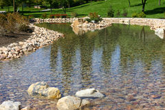 Stream in park. Close-up view of stream of water in rock bed with green grass Royalty Free Stock Image