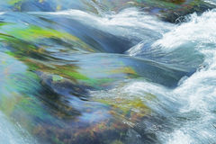 Stream rapids in a river. Smooth water surface with splashes Royalty Free Stock Images
