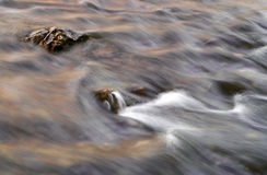 Stream and Rock. A rock in the middle of a rushing stream royalty free stock photo
