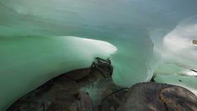 Stream running under the glacier. Stream running under the ice. camera moving by slider. rocky bottom of the stream stock video footage