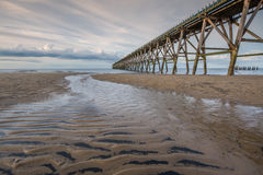 Stream. Small Stream on a Sandy Beach with an Old Pier Royalty Free Stock Photo