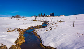 Stream through a snow covered farm field in rural Lancaster Coun Stock Image