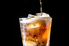 Stream of soda being pouring into a glass with soda and ice cube on black. Background, closeup texture, splashing, splash, fizz Royalty Free Stock Image