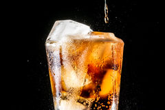 Stream of soda being pouring into a glass with soda and ice cube on black. Background, closeup texture, splashing, splash, fizz Stock Images