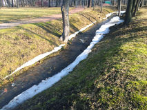 Stream in spring park flows in a frame of thawing snow Stock Photo