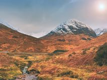 Stream and stony bridge  in spring Higland mountains in Scotland. Snowy mountains in heavy clouds. Royalty Free Stock Photography