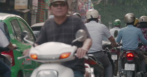 Stream of transport on Hanoi road, Vietnam. HANOI, VIETNAM - OCTOBER 27, 2015: Back view of moving transport stream on the road. Number of motorbikes dominating stock video