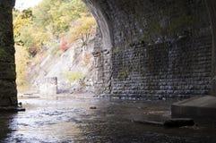 Stream Tunnel under Train Bridge. Autumn stream flowing through tunnel underneath an old train bridge Stock Image