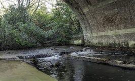 Stream under the bride in Virginia Water, Surrey, United Kingdom. Stream under the bride - Virginia Water, Surrey, United Kingdom Stock Image
