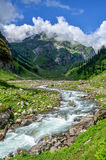 The stream in the valley - Rani nallah. A view of  a valley with mountains, clouds, vegetation and a stream called Rani nallah on first day of Hampta pass trek Stock Photos