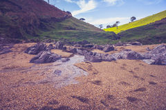 Stream of water on beach near rural landscape Stock Images