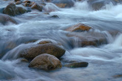 Stream water flowing past stones Stock Photos