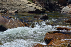 Stream Water Flows By Big Rocks. Water flows over rocks with big boulders in the background Stock Photo