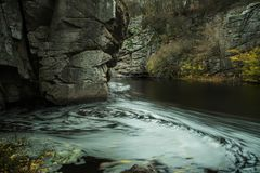 The stream of water in the river flowing between the rocks. In the canyon. Long exposure Stock Photography