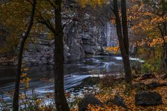 The stream of water in the river flowing between the rocks. In the canyon. Long exposure. Trees with golden leaves on the river bank Stock Image