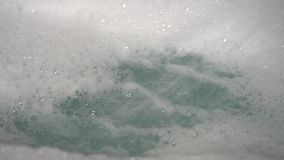 A stream of water from the shower blurs a bunch of foam into the bathtub. Bubbles form and fall
