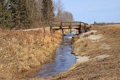 Stream of water under a bridge. Narrow stream of water flowing under old wood bridge royalty free stock image