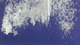 Stream of white bubbles in blue water. Pouring water splashes and creates turbulent bubbles. Underwater stock footage