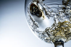 Stream of white wine pouring into a glass Stock Image