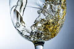 Stream of white wine pouring into a glass Stock Photography