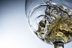 Stream of white wine pouring into a glass, white wine splash on grey background Stock Photo