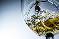 Stream of white wine pouring into a glass, white wine splash on grey background Stock Photos