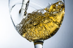 Stream of white wine pouring into a glass, white wine splash on grey background Stock Images