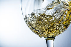 Stream of wine pouring into a glass, white wine splash on grey background Royalty Free Stock Images