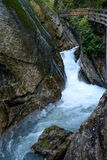 Stream and wooden pier in deep rocky ravine. Stream between rocks and wooden pier in deep ravine in mountains Stock Images