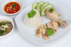 Streamed oily rice and streamed chicken as 'Hainanese chicken rice' s with spicy soy bean sauce on white background. Stock Images